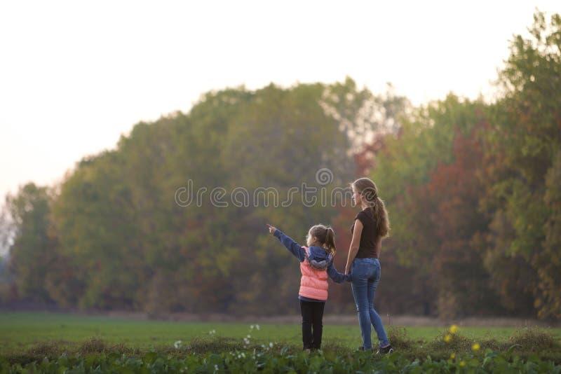 Το κορίτσι μικρών παιδιών δείχνει στο χέρι εκμετάλλευσης απόστασης της ελκυστικής μητέρας στο πράσινο λιβάδι υπαίθρια που απολαμβ στοκ εικόνες