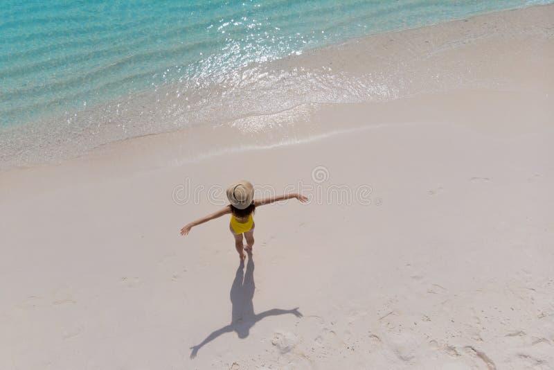 Το κορίτσι μόνο στην ακτή και απολαμβάνει τον ήλιο Η νέα γυναίκα σε ένα καπέλο αχύρου και οι κίτρινες στάσεις μαγιό με τα όπλα στοκ εικόνες