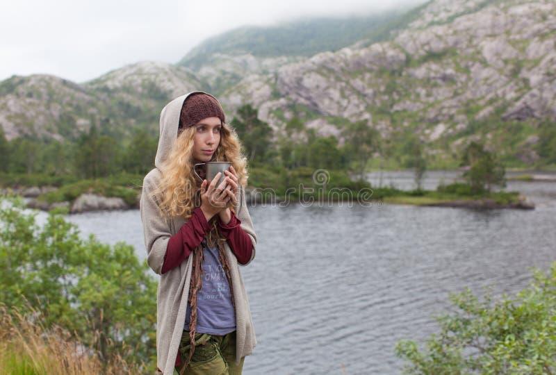 Το κορίτσι ο τουρίστας στα βουνά θέρμανε μια κούπα του θερμού τσαγιού στοκ φωτογραφία