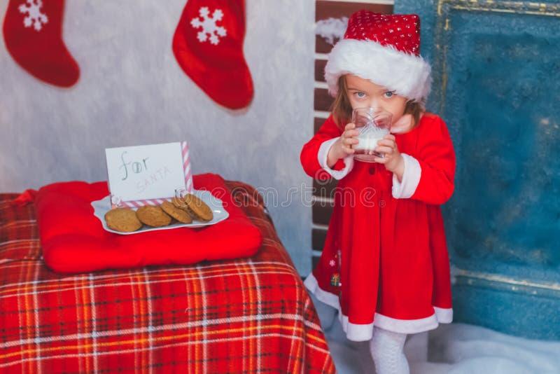 Το κορίτσι πίνει το γάλα στο καπέλο Άγιου Βασίλη στοκ εικόνες