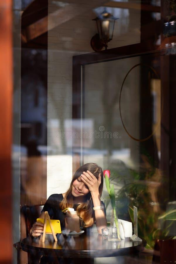 Το κορίτσι πίνει τον καφέ και προσέχει το βίντεο στο κινητό τηλέφωνο στοκ φωτογραφία