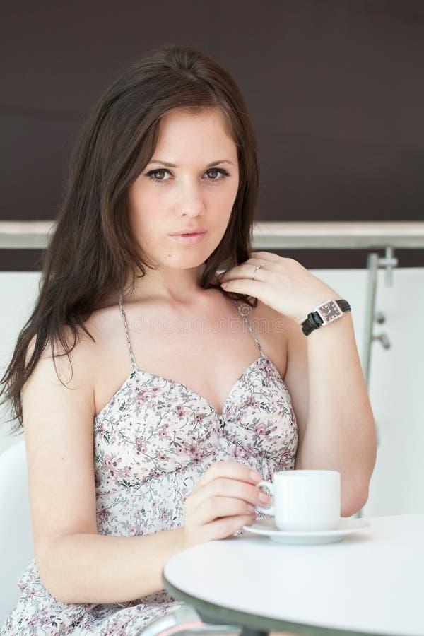 Το κορίτσι πίνει τον καφέ στον καφέ ι στοκ εικόνες