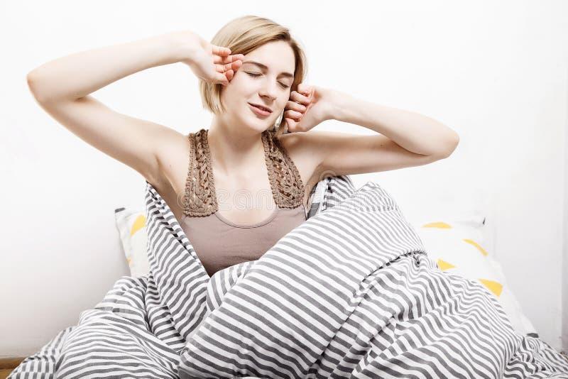 Το κορίτσι πίνει τον καφέ στο κρεβάτι Το κορίτσι πρωινού το νέο κορίτσι ξυπνά το πρωί ύπνος ξυπνώντας πρωί Διαβάζοντας τον Τύπο μ στοκ εικόνα με δικαίωμα ελεύθερης χρήσης
