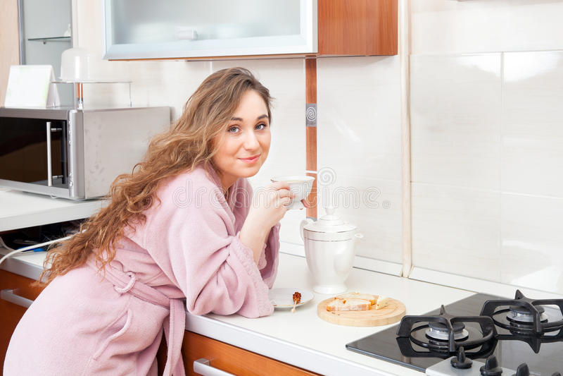 Το κορίτσι πίνει το τσάι στην κουζίνα στοκ φωτογραφίες