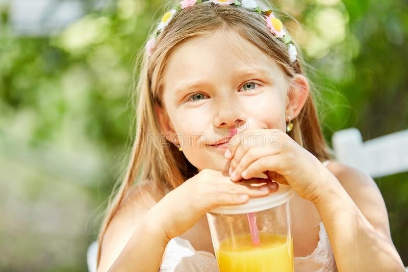 Το κορίτσι πίνει το χυμό από πορτοκάλι με το άχυρο στοκ εικόνα