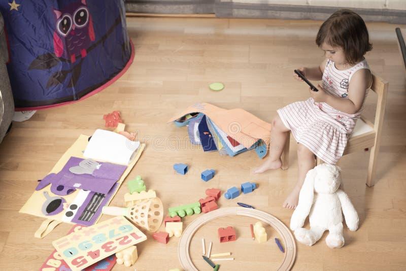 Το κορίτσι παίζει το κινητό τηλέφωνο Το κορίτσι γαντζώνεται στο κινητό τηλέφωνο Δεν παίζει με τα παιχνίδια Το κινητό τηλέφωνο είν στοκ εικόνα