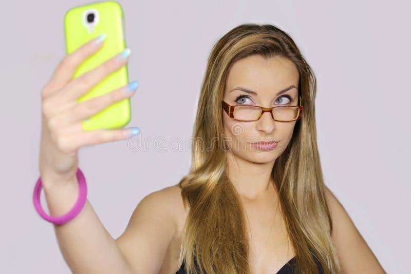 Το κορίτσι παίρνει μια αυτοπροσωπογραφία με το έξυπνο τηλέφωνό της στοκ φωτογραφίες με δικαίωμα ελεύθερης χρήσης