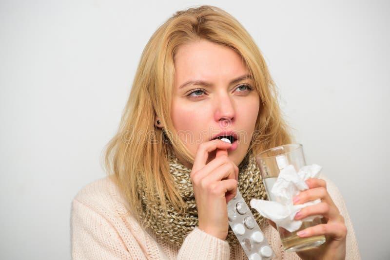 Το κορίτσι παίρνει την ιατρική πίνει το νερό Πονοκέφαλος και κρύες θεραπείες Η γυναίκα η φουσκάλα ταμπλετών λαβής μαντίλι τρίχας  στοκ εικόνες