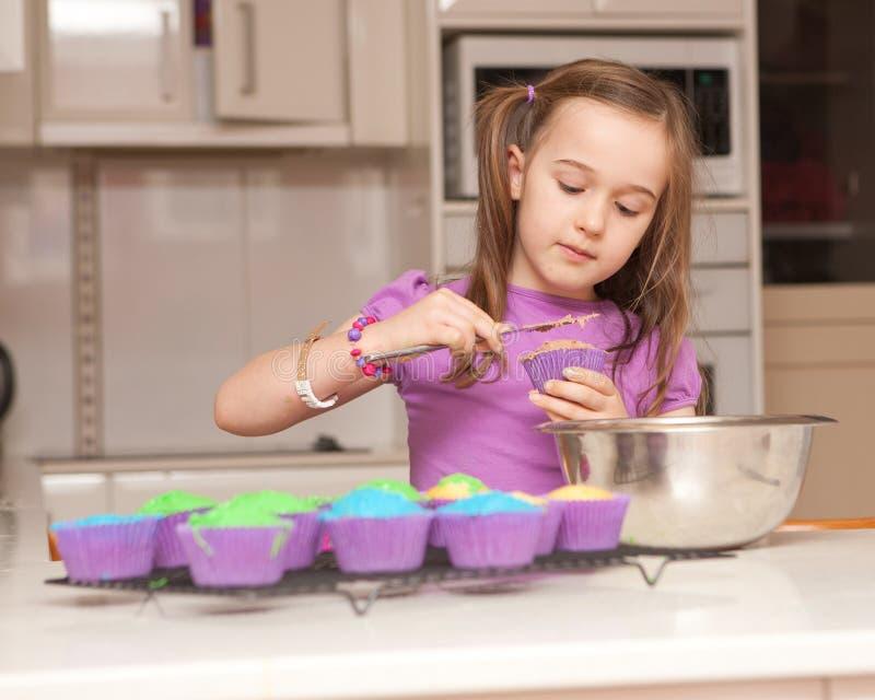 το κορίτσι παγώνει muffins τις νεολαίες στοκ φωτογραφία με δικαίωμα ελεύθερης χρήσης
