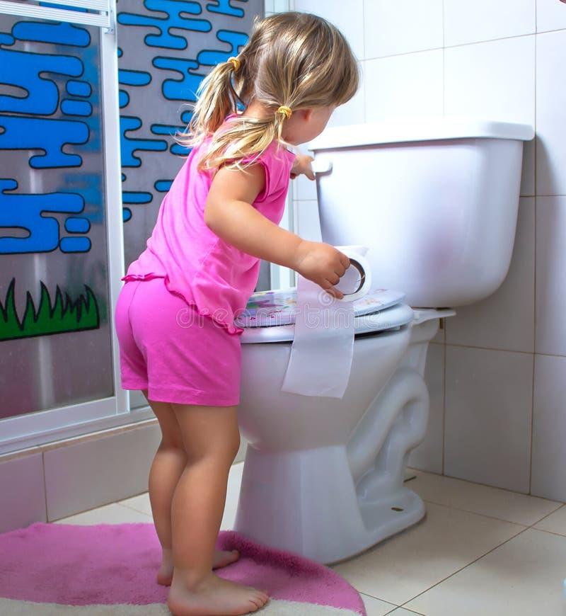 Το κορίτσι το παιδί στέκεται στην τουαλέτα με το χαρτί τουαλέτας στα χέρια στοκ φωτογραφία