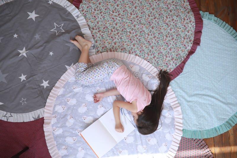 Το κορίτσι παιδιών βρίσκεται και ύπνοι στο χαλί δίπλα στο λεύκωμα στοκ φωτογραφία με δικαίωμα ελεύθερης χρήσης