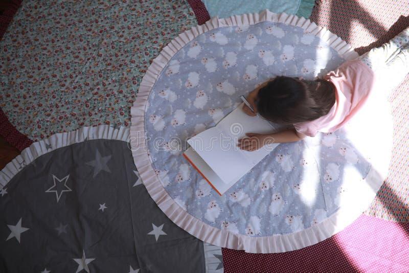 Το κορίτσι παιδιών βρίσκεται στο χαλί και σύρει στο λεύκωμα στοκ εικόνες