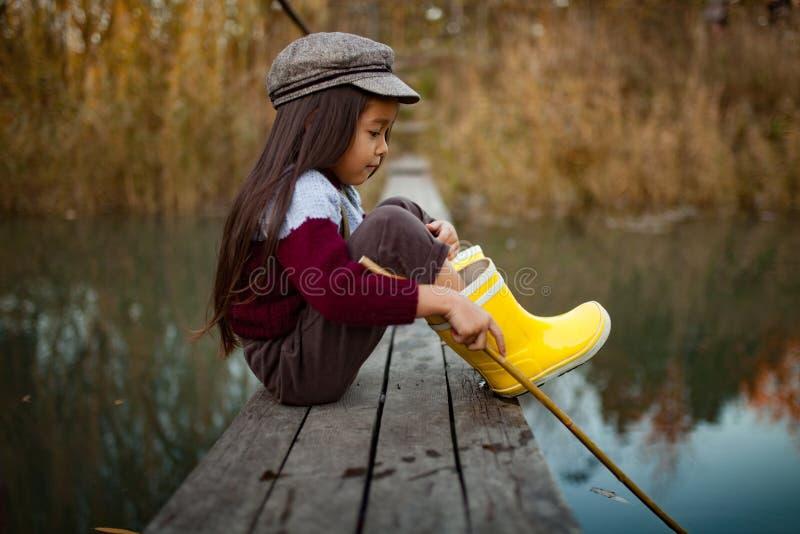 Το κορίτσι παιδιών κάθεται στην ξύλινη γέφυρα αλιείας και πιάνει τα ψάρια με το s στοκ φωτογραφία
