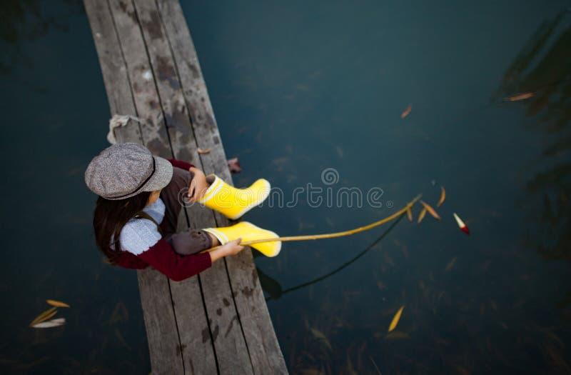 Το κορίτσι παιδιών κάθεται στην ξύλινη γέφυρα αλιείας και πιάνει τα ψάρια με το s στοκ εικόνες