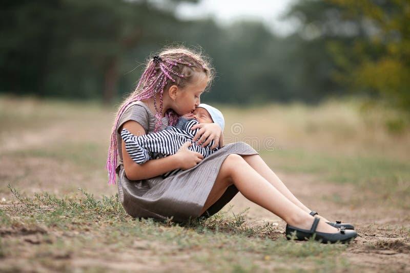 Το κορίτσι παιδιών κάθεται στη χλόη με το νεογέννητο αδελφό της στον περίπατο στην ισοτιμία στοκ φωτογραφίες με δικαίωμα ελεύθερης χρήσης