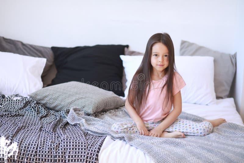 Το κορίτσι παιδιών κάθεται στο κρεβάτι στις πυτζάμες στοκ φωτογραφία