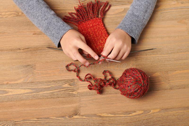 Το κορίτσι παιδιών μαθαίνει να πλέκει ένα μαντίλι Το κόκκινο νήμα μαλλιού είναι στον ξύλινο πίνακα Κινηματογράφηση σε πρώτο πλάνο στοκ εικόνα