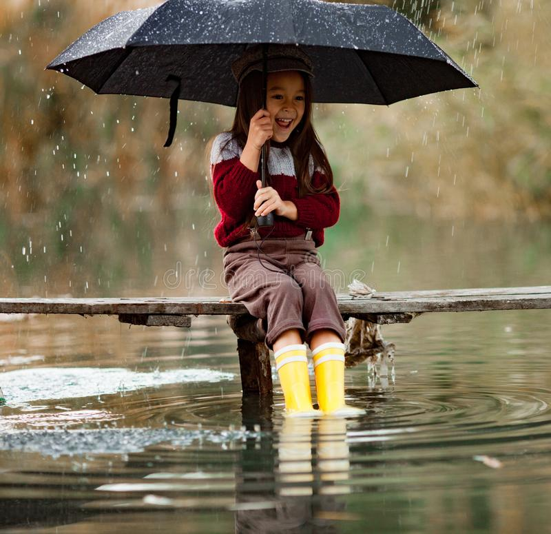Το κορίτσι παιδιών με την ομπρέλα κάθεται στην ξύλινη γέφυρα και laughes στο RA στοκ εικόνες