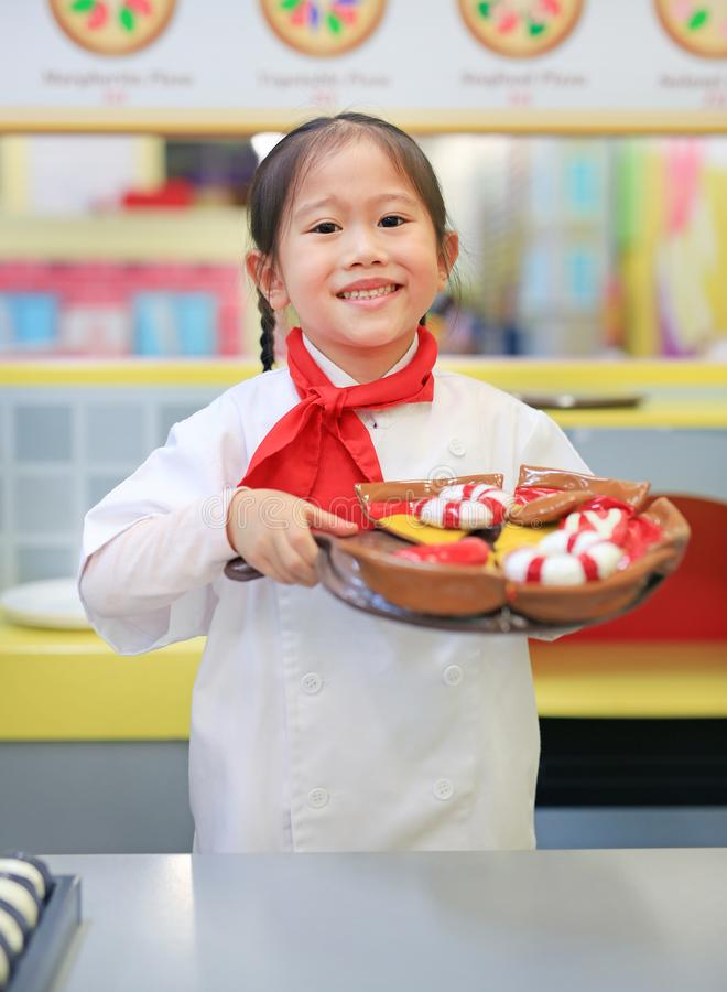 Το κορίτσι παιδιών σε ένα κοστούμι του μικρού αρχιμάγειρα κάνει την πίτσα, που μαγειρεύει την έννοια παιδιών στοκ εικόνες