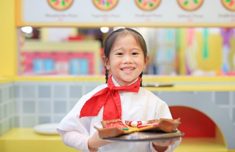 Το κορίτσι παιδιών σε ένα κοστούμι του μικρού αρχιμάγειρα κάνει την πίτσα, που μαγειρεύει την έννοια παιδιών στοκ εικόνα