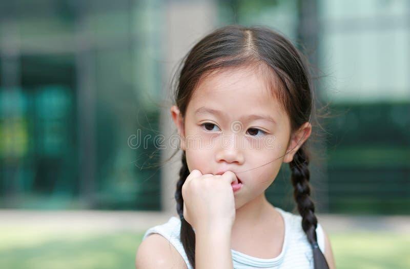 Το κορίτσι παιδιών σκοπεύει την απορρόφηση των δάχτυλών της Οι χειρονομίες των παιδιών που στερούνται την εμπιστοσύνη στοκ εικόνες με δικαίωμα ελεύθερης χρήσης