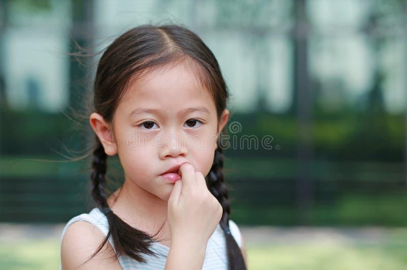 Το κορίτσι παιδιών σκοπεύει την απορρόφηση των δάχτυλών της Οι χειρονομίες των παιδιών που στερούνται την εμπιστοσύνη στοκ εικόνα
