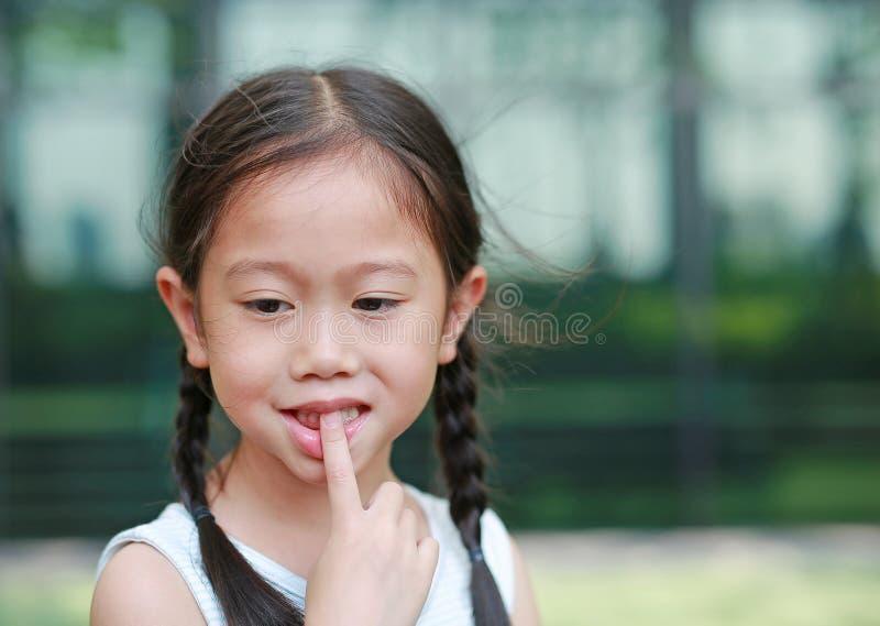 Το κορίτσι παιδιών σκοπεύει την απορρόφηση των δάχτυλών της στοκ φωτογραφία