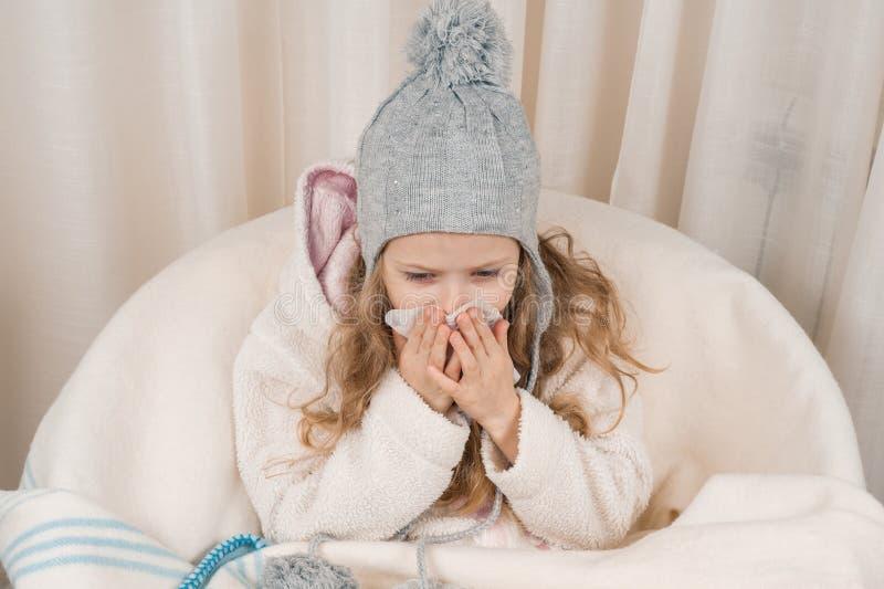 Το κορίτσι παιδιών στο σπίτι στην καρέκλα με το θερμό πλεκτό μάλλινο κάλυμμα καπέλων φτερνίζεται στο χαρτομάνδηλο Χειμερινά κρύα  στοκ φωτογραφία με δικαίωμα ελεύθερης χρήσης