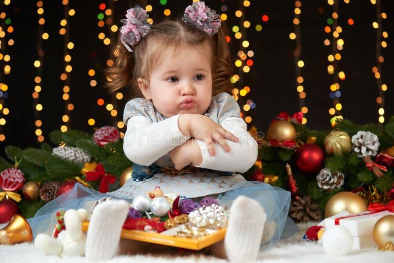 Το κορίτσι παιδιών κρύβει τα παιχνίδια της, το πορτρέτο στη διακόσμηση Χριστουγέννων, την έννοια χειμερινών διακοπών, το σκοτεινό στοκ εικόνα με δικαίωμα ελεύθερης χρήσης