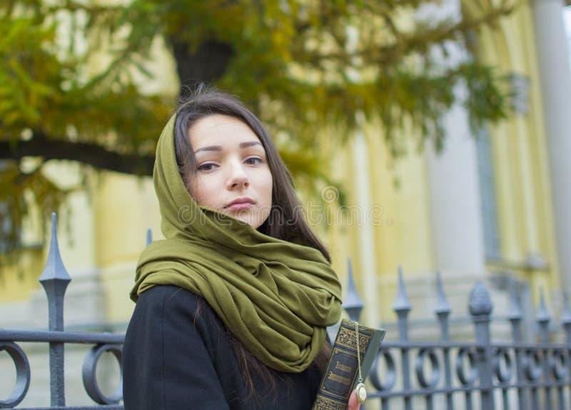 Το κορίτσι περπατά κάτω από την οδό με ένα βιβλίο στοκ φωτογραφίες με δικαίωμα ελεύθερης χρήσης