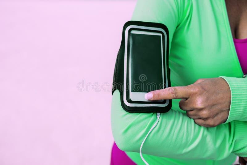 Το κορίτσι πηγαίνει για αθλήματα, χρησιμοποιεί κινητή επικοινωνία στοκ εικόνα