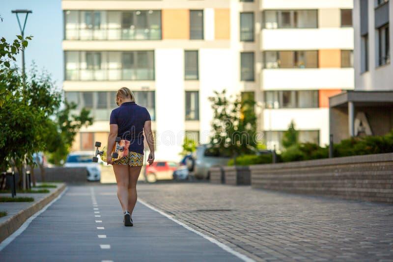 Το κορίτσι πηγαίνει κάτω από το δρόμο κρατώντας ένα longboard στοκ εικόνες με δικαίωμα ελεύθερης χρήσης