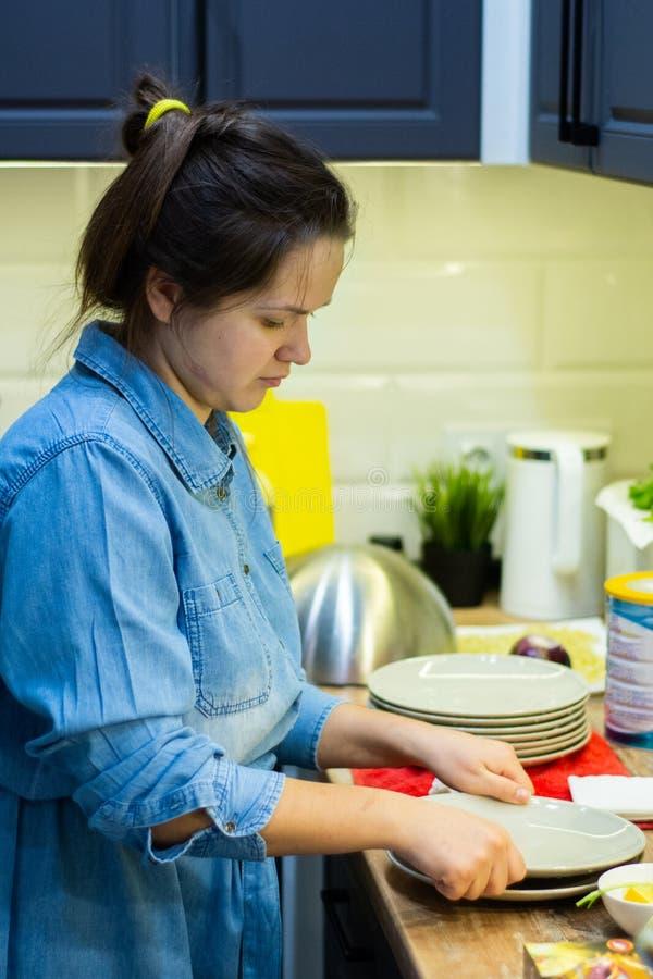 Το κορίτσι πλένει τα πιάτα στην κουζίνα στοκ φωτογραφία με δικαίωμα ελεύθερης χρήσης