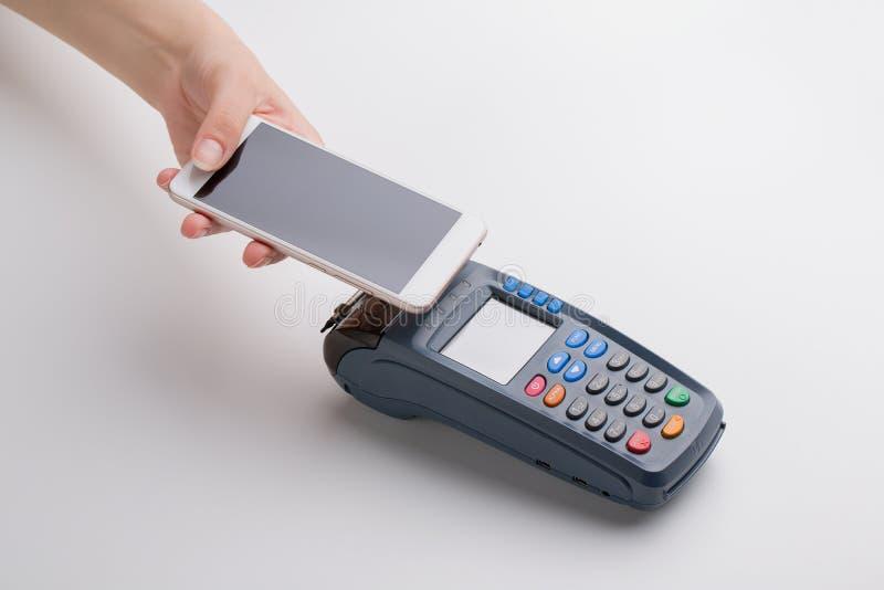 Το κορίτσι πληρώνει την αγορά μέσω του smartphone στοκ εικόνα