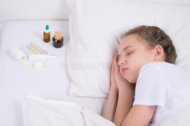 το κορίτσι που είναι άρρωστο και ύπνοι στο κρεβάτι, δίπλα σε την είναι φάρμακα για την αποκατάσταση στοκ εικόνα με δικαίωμα ελεύθερης χρήσης