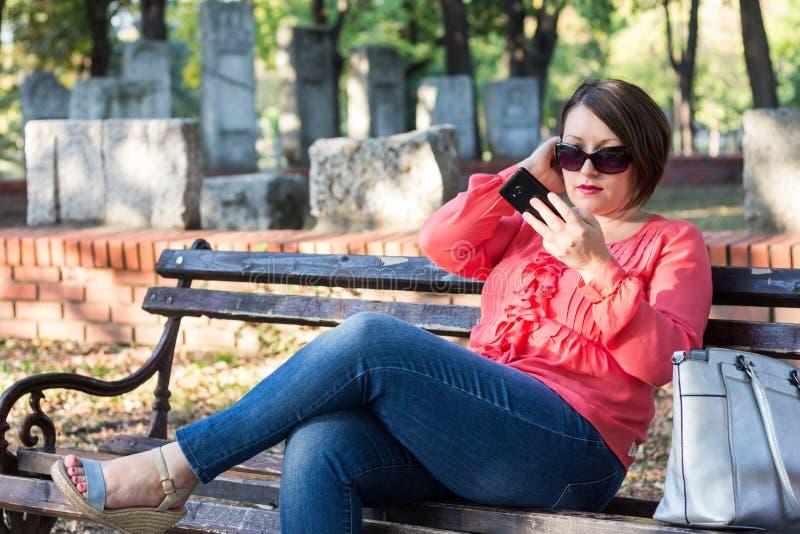 Το κορίτσι που ελέγχει την αποτελεί στο κινητό τηλέφωνο της στοκ εικόνες με δικαίωμα ελεύθερης χρήσης