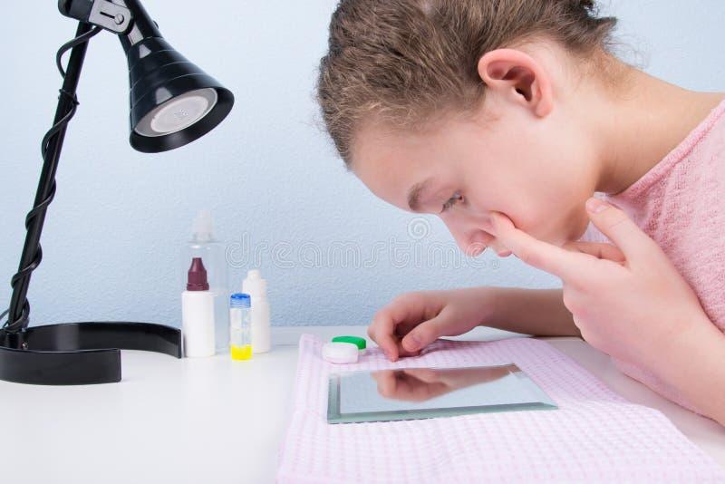 Το κορίτσι, που κάθεται στον πίνακα σε έναν ειδικό καθρέφτη, βάζει στους φακούς επαφής για να βελτιώσει το όραμα στοκ εικόνες
