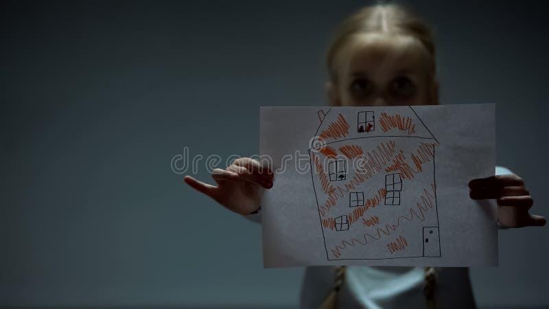 Το κορίτσι που παρουσιάζει εικόνα σπιτιών στη κάμερα, ορφανό παιδί χρειάζεται το σπίτι και την οικογένεια στοκ φωτογραφίες