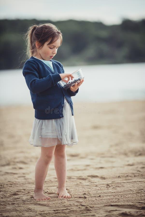 Το κορίτσι που τρώει τα βακκίνια από ένα κύπελλο γυαλιού στοκ φωτογραφία με δικαίωμα ελεύθερης χρήσης