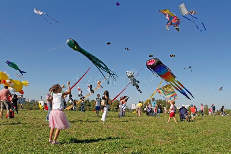 Το κορίτσι προωθεί έναν ικτίνο στον ουρανό στο φεστιβάλ ικτίνων στο πάρκο Tsaritsyno στη Μόσχα στοκ εικόνες