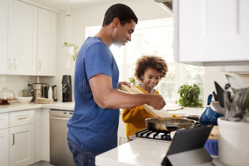 Το κορίτσι προ-εφήβων και ο πατέρας της που στέκονται hob στην κουζίνα που προετοιμάζει τα τρόφιμα σε ένα τηγανίζοντας τηγάνι, με στοκ φωτογραφίες
