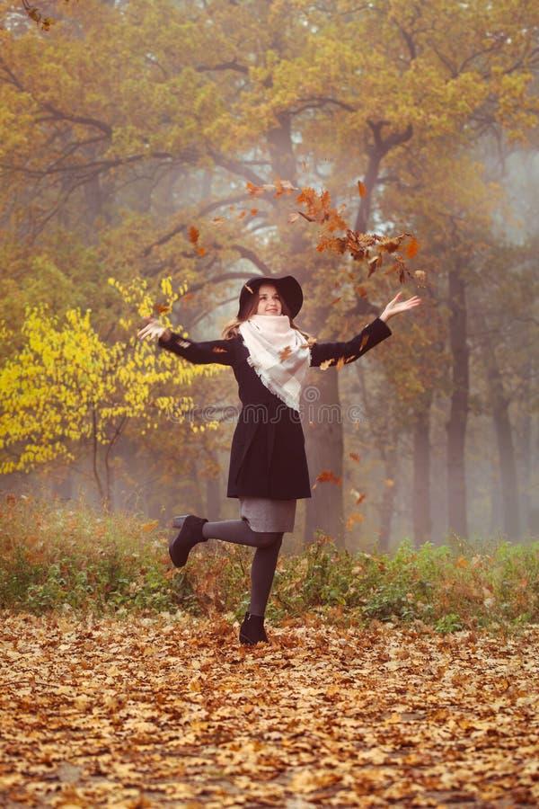 Το κορίτσι ρίχνει επάνω στα φύλλα στοκ εικόνες με δικαίωμα ελεύθερης χρήσης