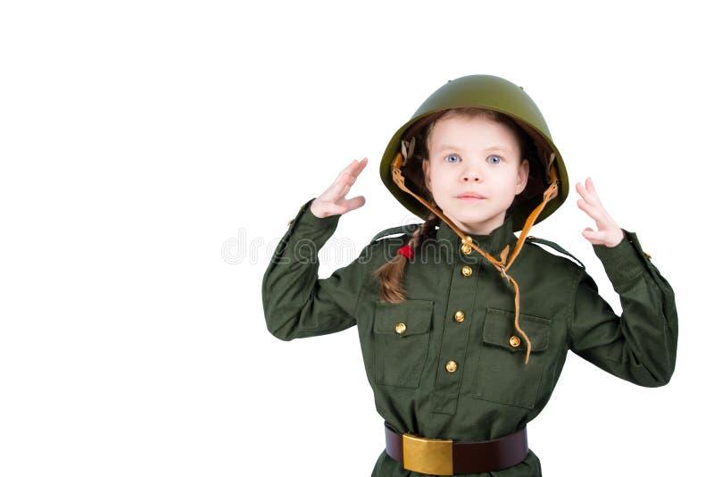 Το κορίτσι σε ένα άσπρο υπόβαθρο, που φορά τα στρατιωτικά ενδύματα και ένα σκληρό καπέλο, φαίνεται έκπληκτο στοκ εικόνες με δικαίωμα ελεύθερης χρήσης