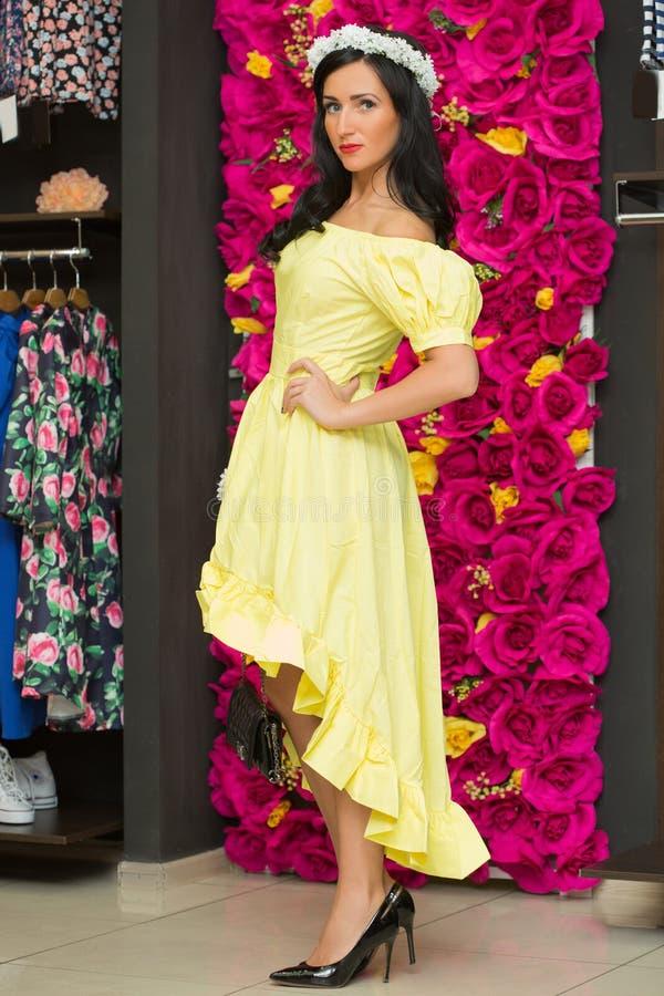 Το κορίτσι σε ένα κίτρινο φόρεμα σε ένα κατάστημα ιματισμού στοκ φωτογραφία