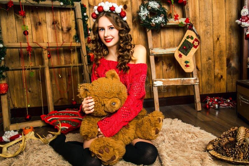Download Το κορίτσι σε ένα κόκκινο πουλόβερ κάθεται με μια Teddy αρκούδα Χριστούγεννα και νέος Στοκ Εικόνες - εικόνα από teddy, τοίχοι: 62705064
