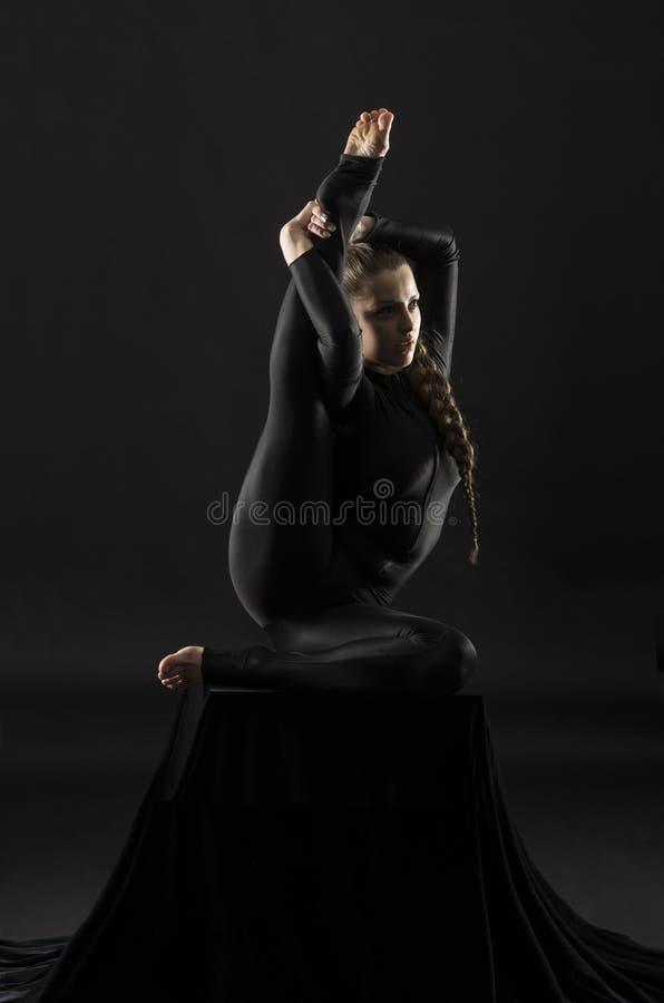 Το κορίτσι σε ένα μαύρο κοστούμι με μακρυμάλλη, εκτελεί τις γυμναστικές ασκήσεις στοκ φωτογραφίες με δικαίωμα ελεύθερης χρήσης