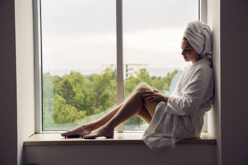 Το κορίτσι σε ένα μπουρνούζι και μια πετσέτα στο κεφάλι κάθεται στο παράθυρο στοκ εικόνα με δικαίωμα ελεύθερης χρήσης