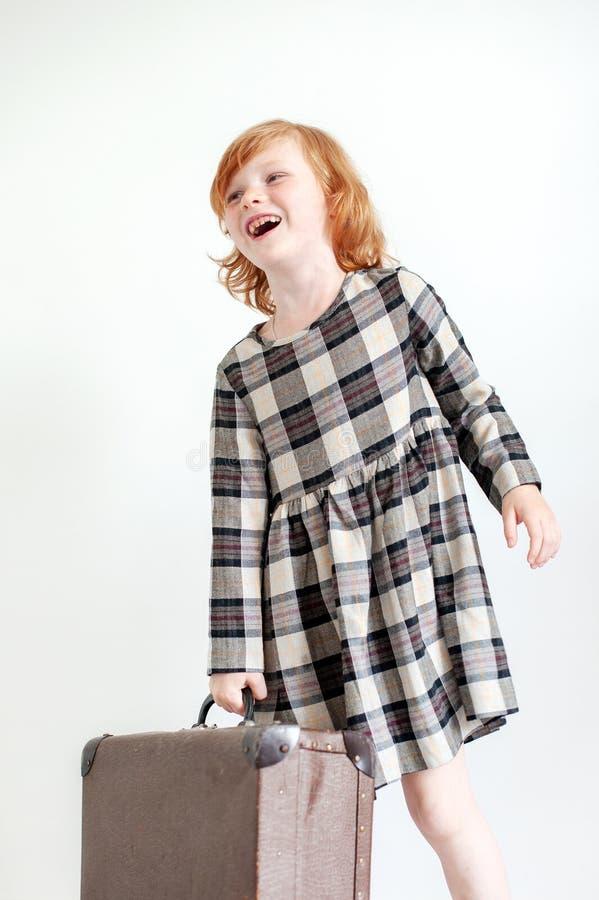 Το κορίτσι σε ένα φόρεμα καρό κρατά μια βαλίτσα και ένα γέλιο στοκ φωτογραφία με δικαίωμα ελεύθερης χρήσης