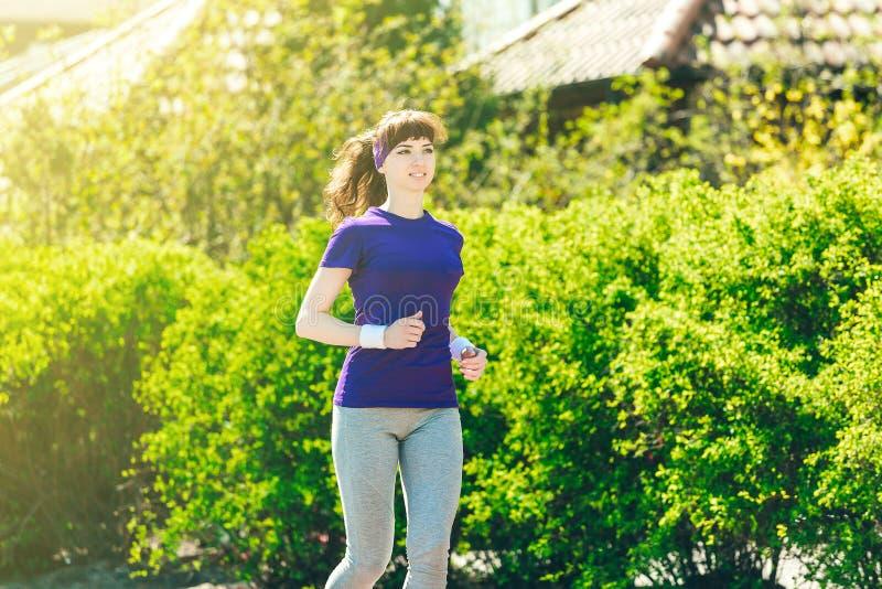 Το κορίτσι σε μια μπλε μπλούζα κάνει τον αθλητισμό στη φύση ενάντια στο σκηνικό των θάμνων jogging νεολαίες γυναικών πάρκ&om στοκ εικόνες