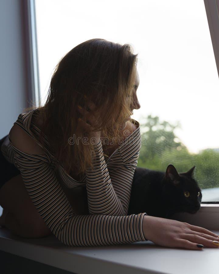 Το κορίτσι σε μια φούστα και μια γάτα κάθονται στο παράθυρο στο βράδυ οδών στοκ εικόνες